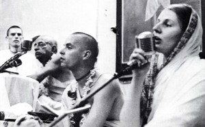 Srimati Haimavati devi dasi, initiated disciple of Srila Prabhupada's, lecturing to women present at one of the large meetings in India. Left to right: Hamsaduta dasa, Srila Prabhupada and Kirtanananda Svami.