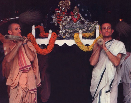 Carrying Sri Sri Radha-Madhava in an ornate palanquin, Pankananghri dasa and Jananivasa dasa emerge from the temple building
