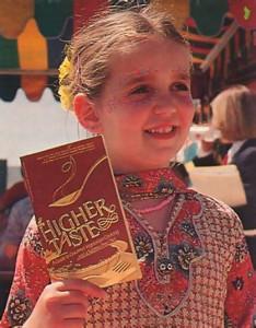 A young devotee offers ISKCON's Higher Taste vegetarian cookbook to passersby.