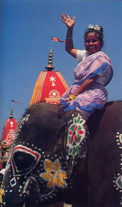 A joyous celebrant surveys the festival scene from a painted mascot.