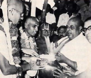Sri Rangam temple leaders greet the ISKCON pada-yatra with a traditional purna-kumbha reception-leaves and flowers in a pot. From left to right: pada-yatra leadersJayadvaita Swami and Lokanatha Swami; Sri Thirumalai Iyengar, head of the temple priests; Sri N. Rangaraja Bhattar, member of the temple advisory committee, formerly chief priest for forty years; and Dr. Gopinatha Rao, the temple's chief administrator.