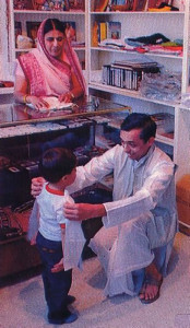 At the temple boutique, a father and son who are part of the temple's Indian community size up some imported devotional clothing.