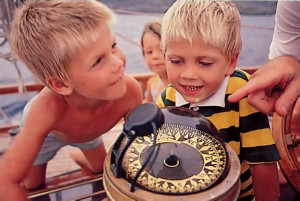 Children receive an impromptu lesson about the ship's compass during a Saturday cruise
