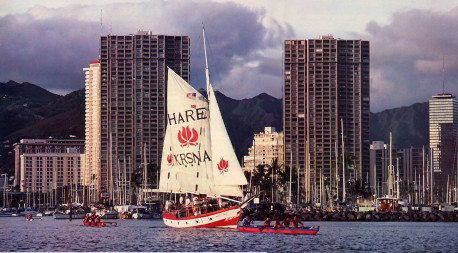Traditional Hawaiian outriggers flank the Jaladuta II as she leaves the Honolulu harbor for an evening cruise